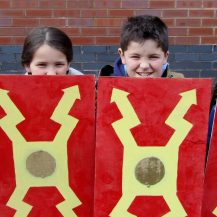 Kids holding roman shields